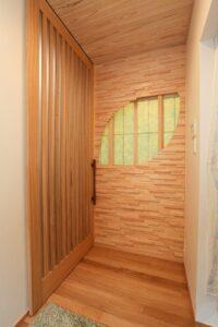 玄関正面手造り葉っぱの形をした灯り取りと大きなドア